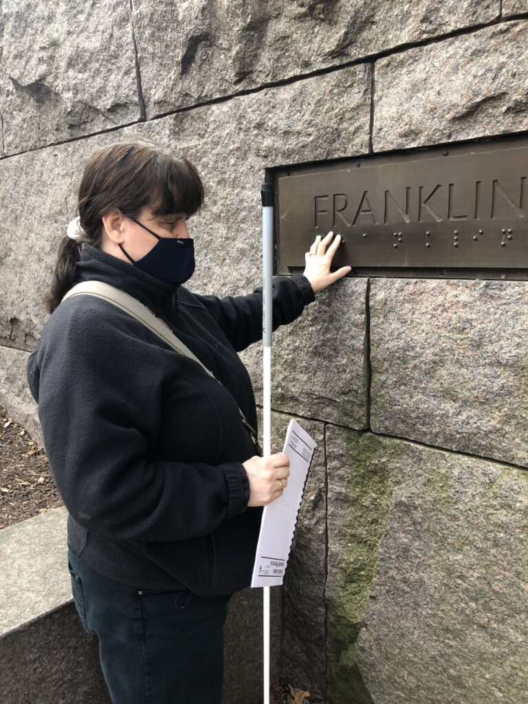 Dr. Fogle-Hatch touching Braille on the wall of the FDR Memorial
